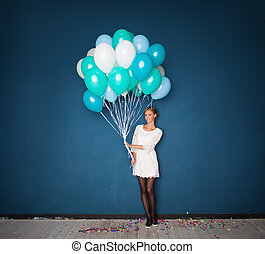 Happy Young Woman in White Dress Holding Balloons on Blue Holiday Background with Confetti
