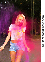 Happy young woman in white t shirt and jeans shorts posing with red Holi powder