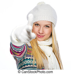 Happy young woman in winter clothes pointing in camera