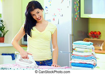 happy young woman ironing clothes at home