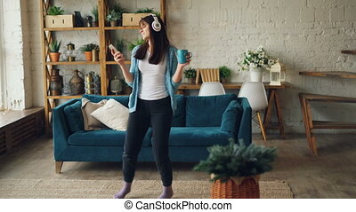 Happy young woman is dancing at home with mug and smartphone...