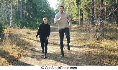 Happy young woman is doing sports with her handsome boyfriend jumping in park on path and laughing enjoying freedom, healthy activity and beautiful nature.