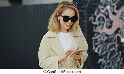 Happy young woman is using smartphone texting her friend and smiling standing outdoors in modern city with graffiti painting in background. People and technology concept.