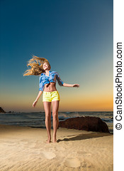 Happy young woman jumping on beach