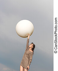 happy young woman jumping with balloon