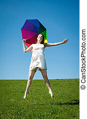 Happy young woman jumping with colorful umbrella