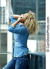 Happy young woman laughing on phone with hand in hair