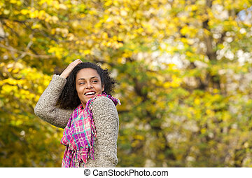 Happy young woman laughing with hand in hair