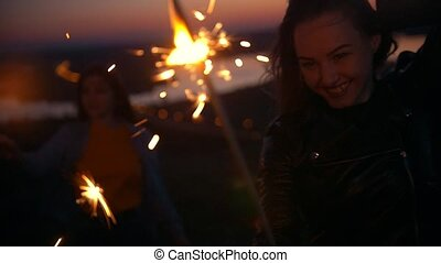 Happy young woman laughing with sparkler on a hill in summer...