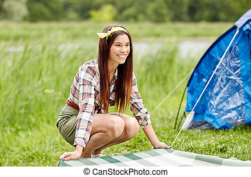happy young woman laying blanket at campsite