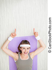 Happy young woman laying on fitness mat and pointing on copy space