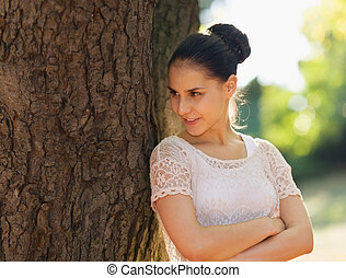 Happy young woman lean against tree and looking on copy space