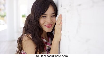 Happy young woman leaning on a white wall