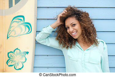 Happy young woman leaning on surfboard