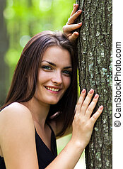 Happy young woman leaning on tree trunk
