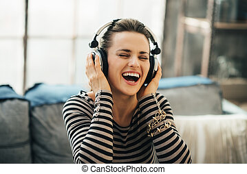 Happy young woman listening music in loft apartment - ...