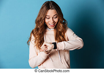 Happy young woman looking aside at watch on hand.
