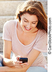 happy young woman looking at cellphone