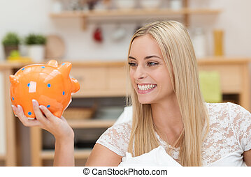 Happy young woman looking at her piggy bank
