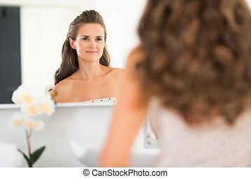 Happy young woman looking in mirror in bathroom