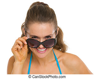 Happy young woman looking out from sunglasses