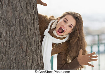 Happy young woman looking out from tree in winter park