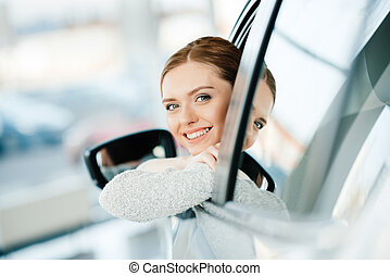 Happy young woman looking out window of new car