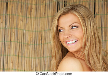 Happy young woman looking over shoulder and smiling