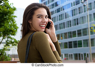 Happy young woman looking over shoulder with phone