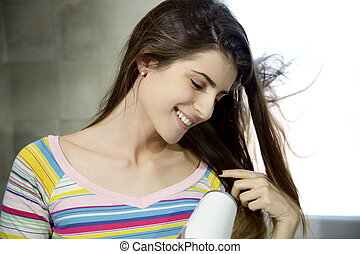 Happy young woman looking silky hair while blow drying at home