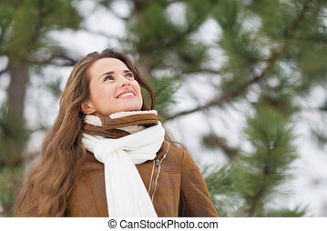 Happy young woman looking up on copy space in winter outdoors