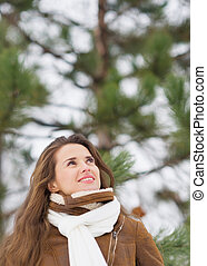 Happy young woman looking up on copy space in winter park