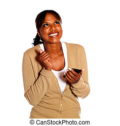 Happy young woman looking up with cellphone