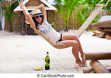 Happy young woman lying in hammock on tropical beach
