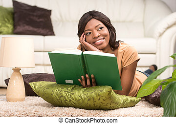 Happy Young Woman Lying On Carpet. Young girl lying on carpet and reading book