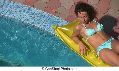 woman lying on inflatable mattress near water pool - happy...