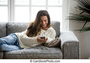 Happy young woman lying on sofa at home using smartphone