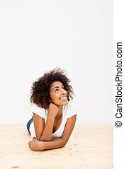Happy young woman lying on the floor daydreaming