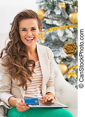 Happy young woman making online shopping with tablet pc near christmas tree