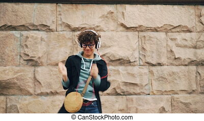 Happy young woman melomaniac is singing and dancing listening to music in headphones and holding smartphone outdoors in the street. Songs and youth concept.