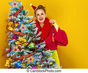 happy young woman near Christmas tree decorating