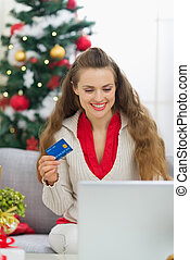 Happy young woman near Christmas tree making online purchases