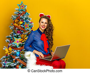 happy young woman near Christmas tree sitting with laptop