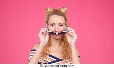 Young woman on a pink background with sunglasses - Happy...