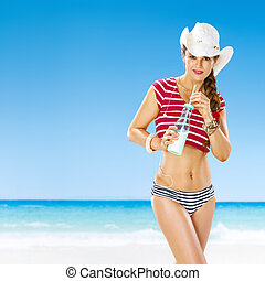 happy young woman on beach with smoothie