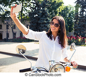 woman on scooter making selfie photo