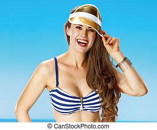 happy young woman on seashore straightening yellow sun visor...