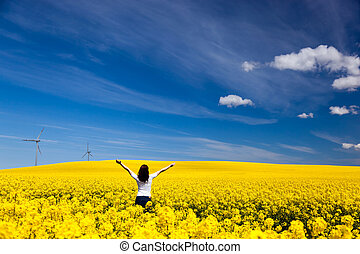 Happy young woman with hands raised on spring field of yellow flowers, rape. Blue sunny sky. Concepts of success, happiness, harmony, health, ecology