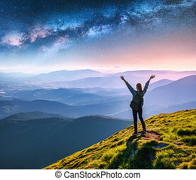 Happy young woman on the mountain peak and arched Milky Way