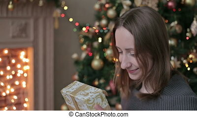 Happy young woman opening Christmas present box